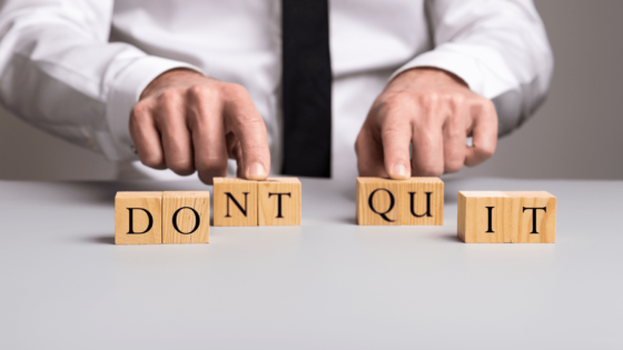 """Wooden blocks on a desk spelling out """"Don't quit'"""